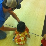 Daddy teaching her how to bowl