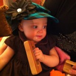 Modeling her new hat and rattle