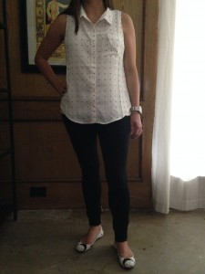 White sleeveless dotted blouse, black skinny pants, and white patterned shoes